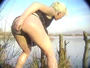 Blonde has anal sex by a lake